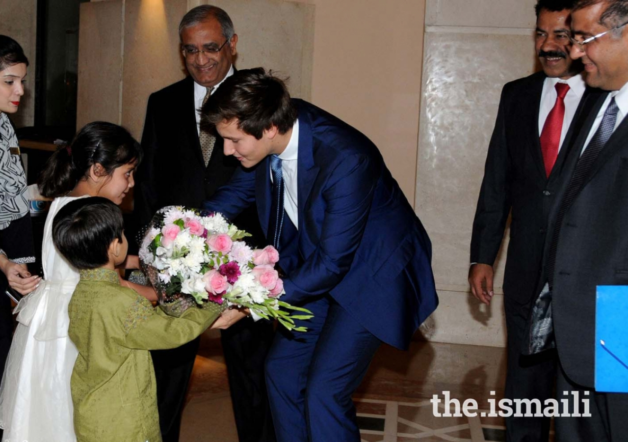 Prince Aly Muhammad is presented a bouquet of flowers upon his arrival at Islamabad Serena Hotel