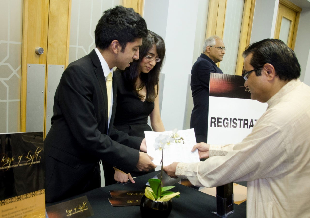 RAYS OF LIGHT ambassadors assist a member of the Edmonton Jamat to register in advance of the exhibition's Canadian premiere.