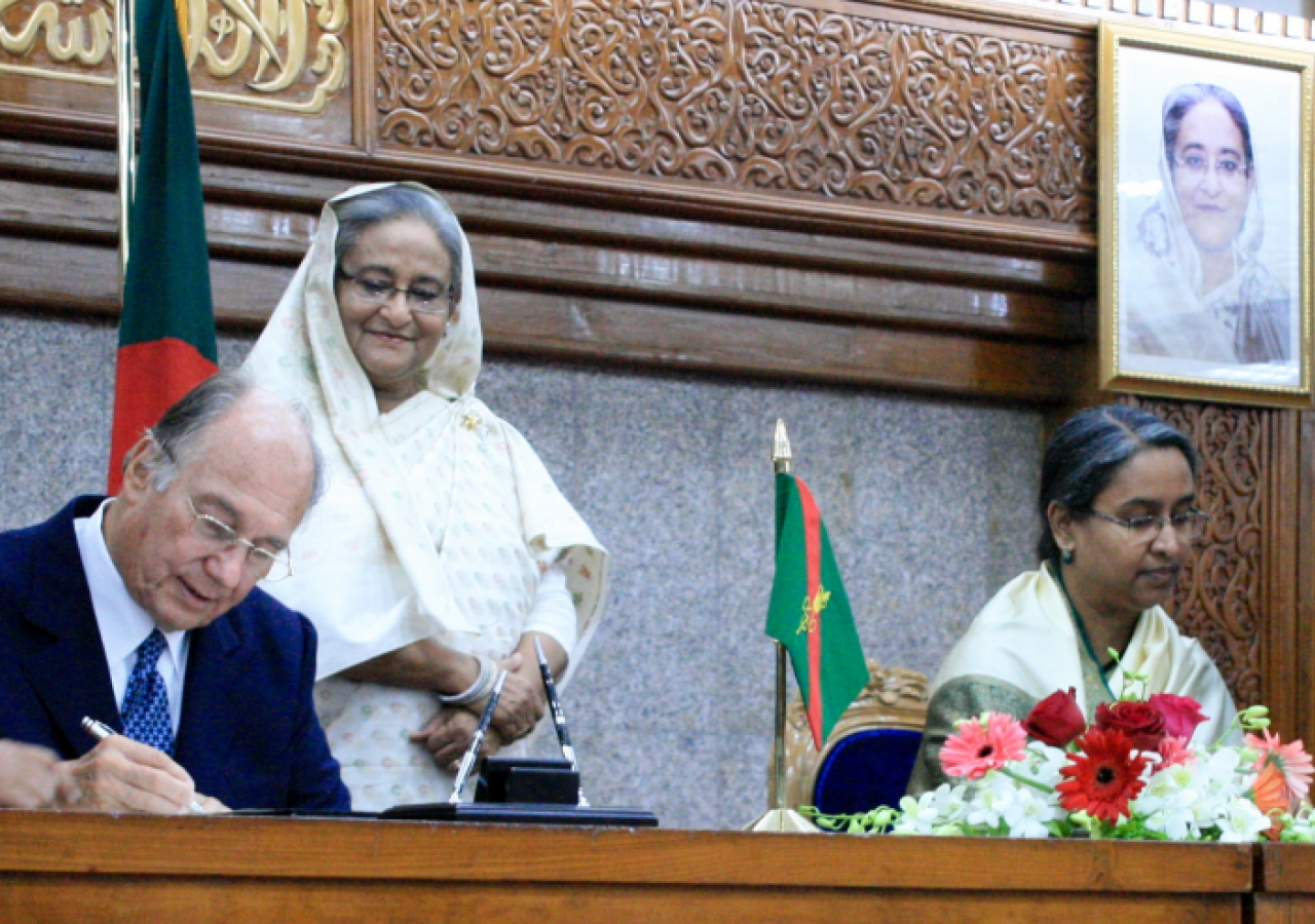 Mawlana Hazar Imam signs a protocol agreement with Foreign Minister Dr Dipu Moni between AKDN and the Government of Bangladesh, as Prime Minister Sheikh Hasina looks on.