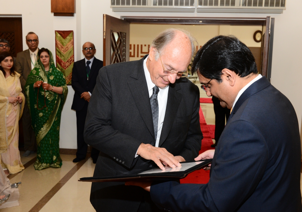 "President Ajanee presents Mawlana Hazar Imam with a 19th century Indian dervish staff with a handle formed in the calligraphic name of Ali, and inscriptions that read ""Ya Ali Madad"" and ""Huwa Ya Ali Madad"". The gift was presented a"
