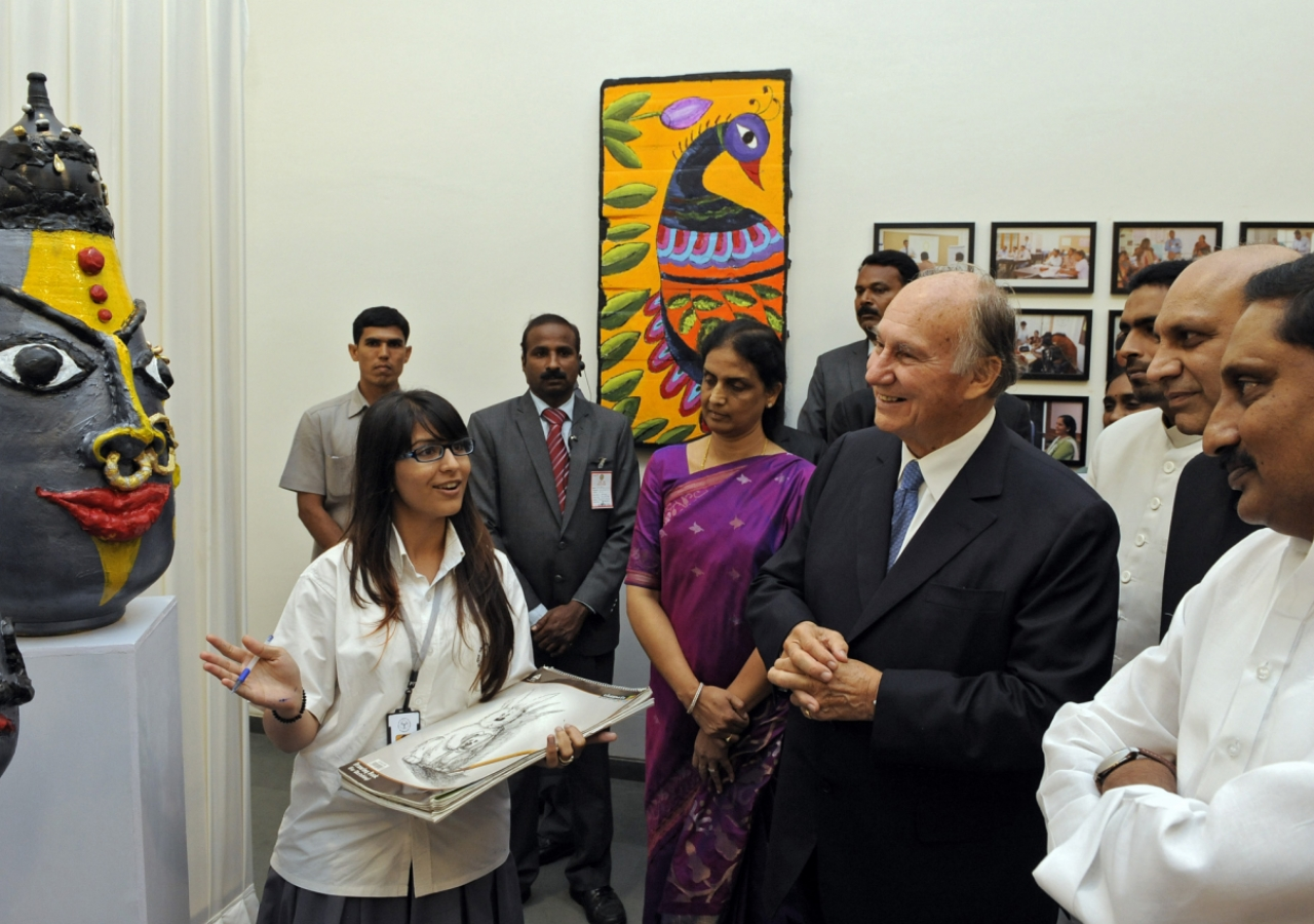 Mawlana Hazar Imam, accompanied by the Chief Minister of Andhra Pradesh and India's Minister for Human Resource Development reviews artwork produced by a student at the Aga Khan Academy, Hyderabad.