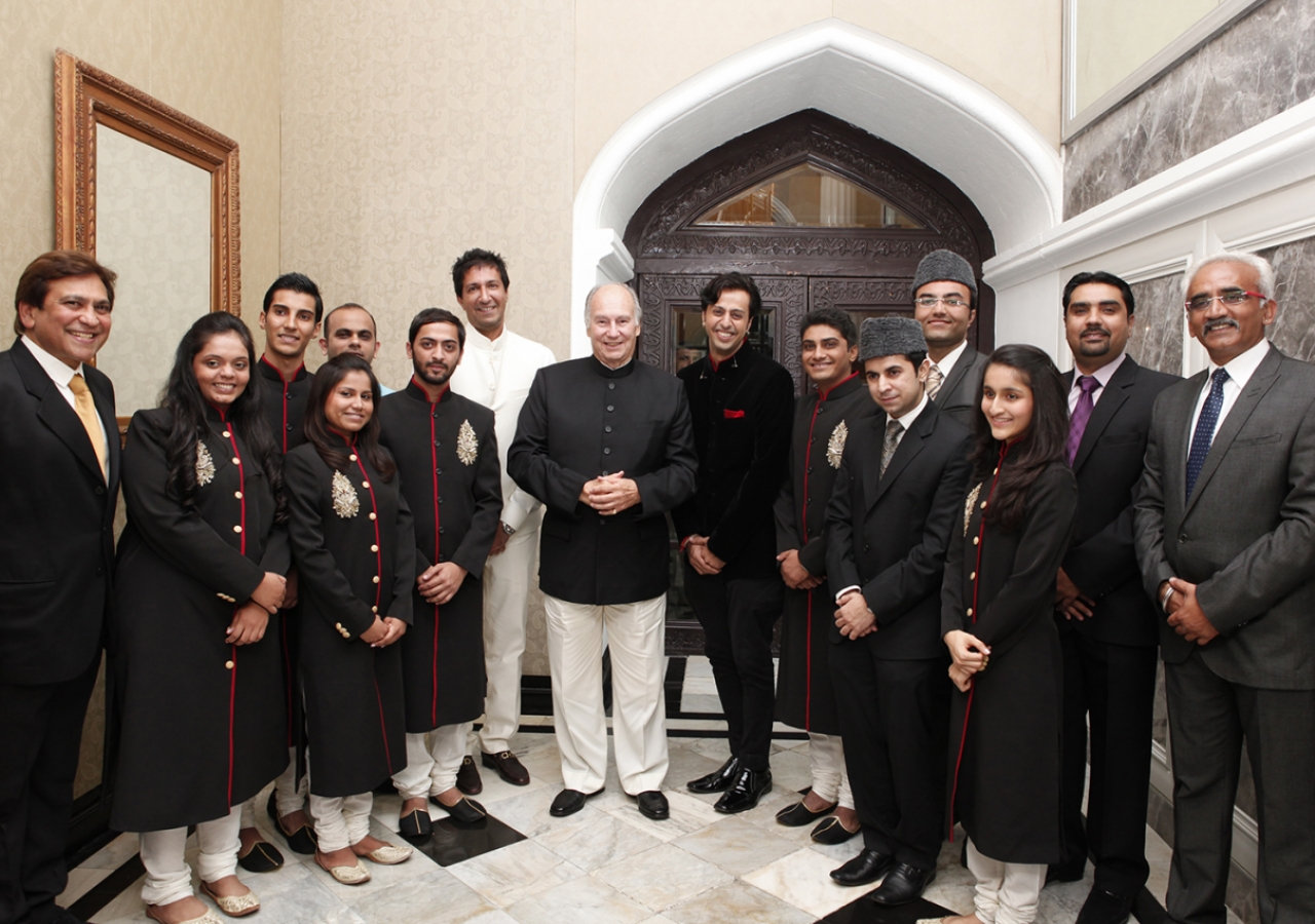 Mawlana Hazar Imam poses for a photograph with the performers at the conclusion of the institutional dinner.
