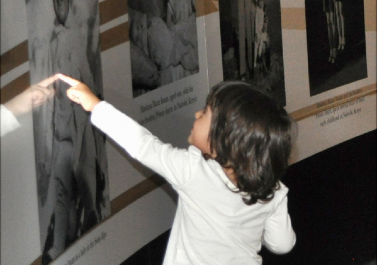 A young visitor delights in a photograph of Mawlana Hazar Imam as a baby.