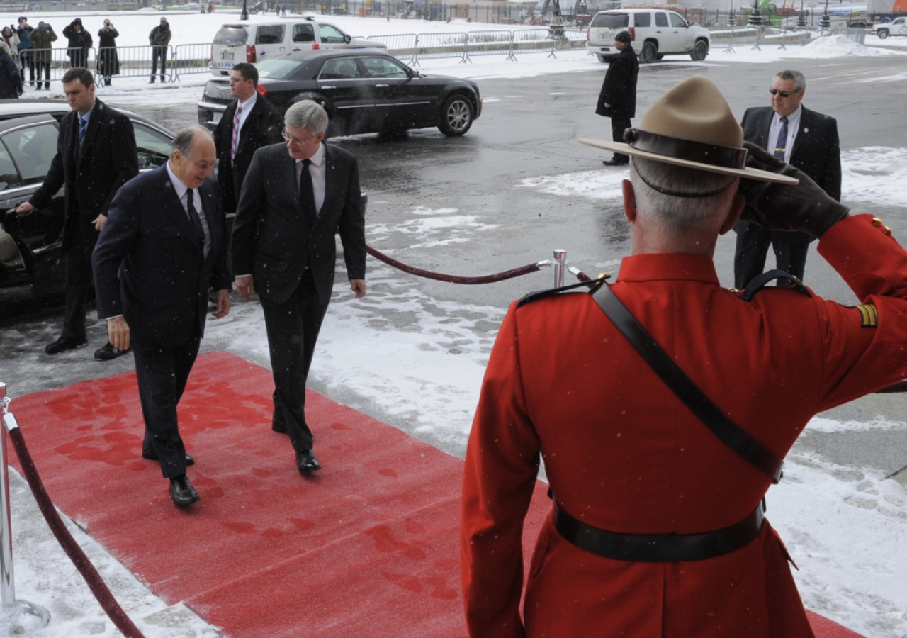 An officer of the Royal Canadian Mounted Police salutes Mawlana Hazar Imam and Prime Minister Stephen Harper at Parliament Hill.
