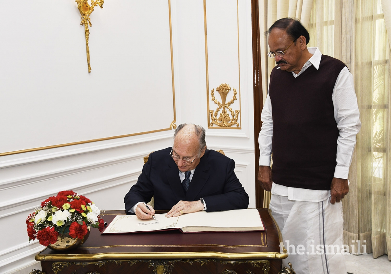 Mawlana Hazar Imam signs the visitors book at the Hyderabad House in New Delhi as Vice President Shri M. Venkaiah Naidu looks on.