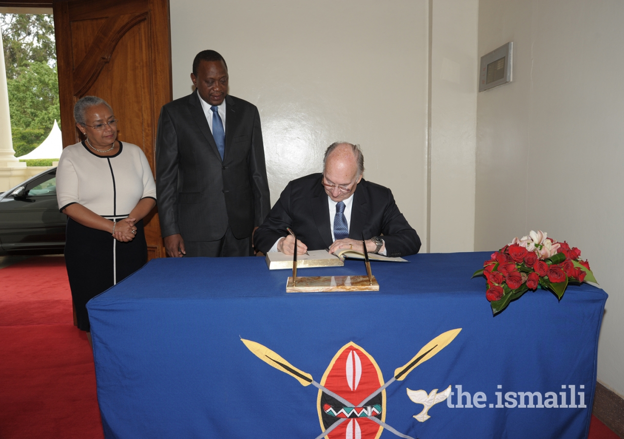 Mawlana Hazar Imam signs the guest book at the State House in Nairobi as His Excellency President Uhuru Kenyatta and First Lady Margaret Kenyatta look on.