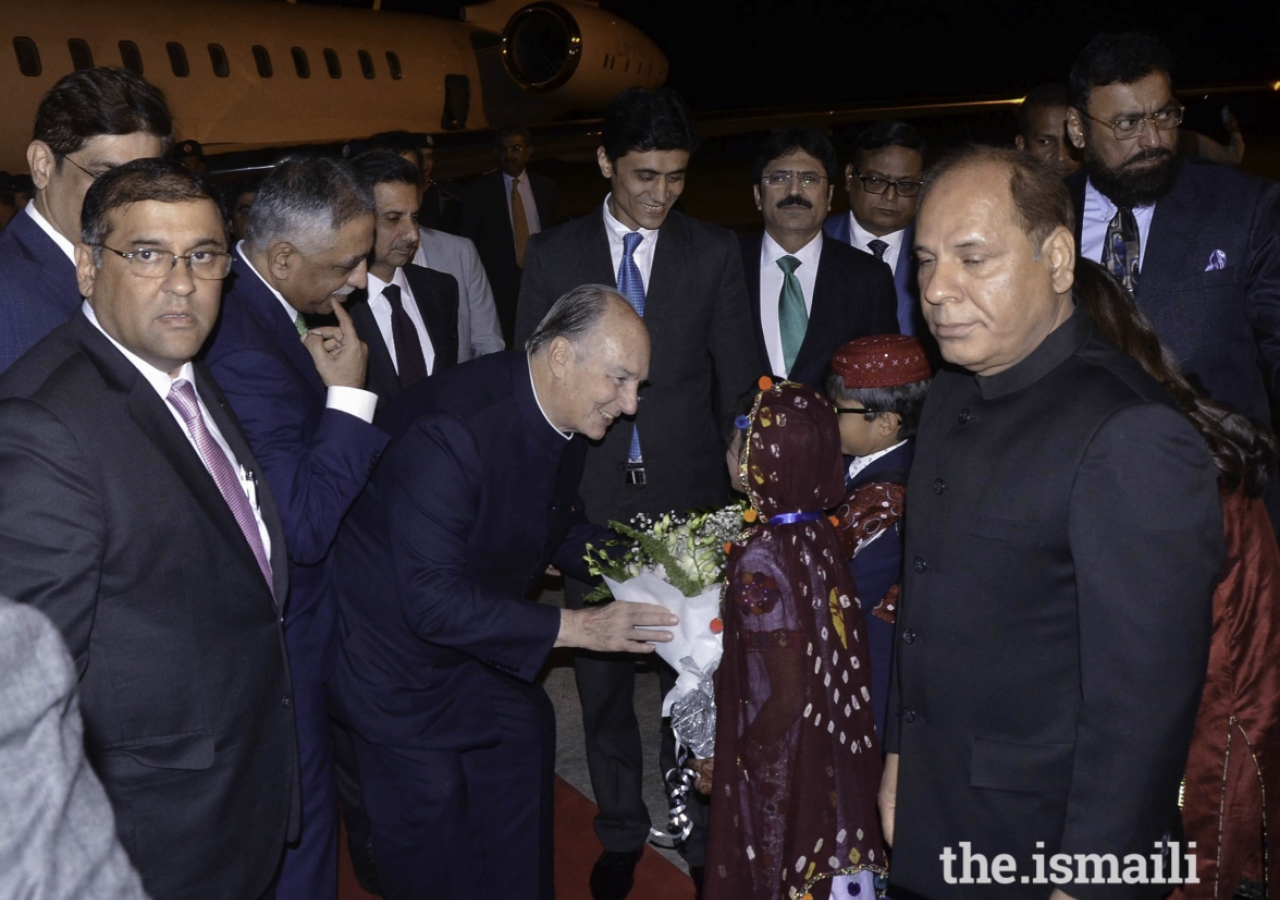 Mawlana Hazar Imam is presented with a bouquet of flowers upon his arrival in Karachi