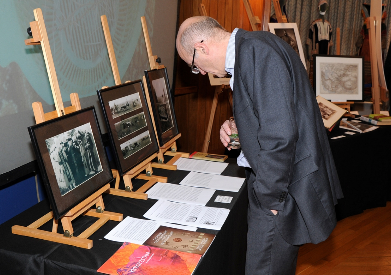 "A visitor examines albums and portraits on display as part of the ""Across Time and Space"" exhibition. Riaz Kassam"