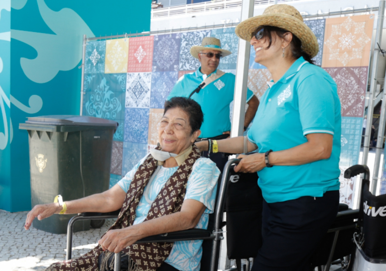 Elderly Jamati members are assisted by volunteers on wheelchair duty.