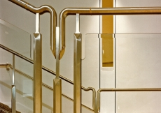 Detail of the handrail in stainless steel, brass and plate glass, which runs along the main stair.