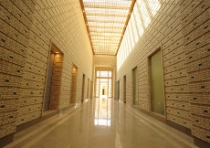 A view down the axial corridor of the administration area from the main entrance of the building. The changing play of light and shade created by sunlight filtering through a wooden lattice, forms patterns on the walls and floor that follow the movement o