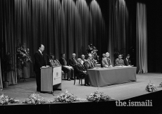 Following the presentation of the diplomas, Mawlana Hazar Imam addresses the new graduates at the University of London Institute of education. Seated at the front table with members of the Board of Governors of the Institute of Ismaili Studies (behind) are Mr. Dennis Lawson, Director of the Institute (left) and Mr. William Taylor, Principal of the University of London (right), July 1983.