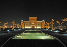 An evening view of the Ismaili Centre, Dushanbe. Pedestrian walkways line the cascading water feature, leading to the building's Main Entrance.