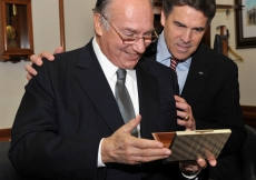 Mawlana Hazar Imam opens a gift presented to him by Governor Perry as the Texas Governor looks on.