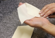 3. Hold the two sheets of pastry in one hand, the top of the roof should be at the top of your hand. Using the other hand, fold one edge over.