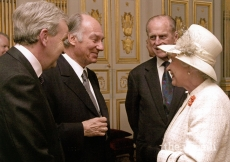"Mawlana Hazar Imam being invested ""Knight Commander of the British Empire"" (KBE) by Queen Elizabeth II on 5 April 2004. Duke Edinburgh is overlooking."