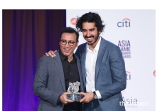 Aasif Mandvi presents Dev Patel with an Asia Game Changer Award.