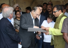 Mawlana Hazar Imam points out details on an archival photograph of the Qutb Shahi Heritage Park with Prince Aly Muhammad and Iliyan watching closely. AKDN / Ahmed Charania
