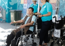 Elderly Jamati members are assisted by volunteers on wheelchair duty.