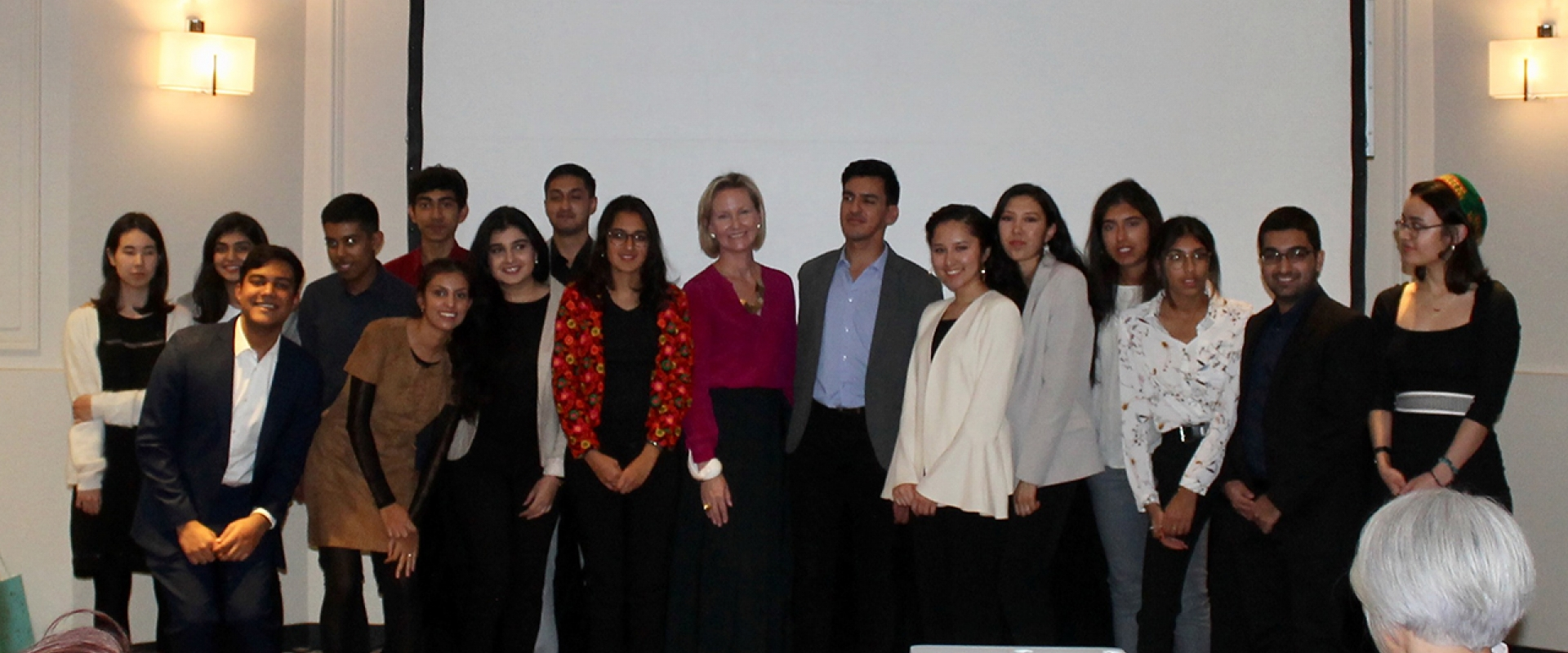 Meredith Preston McGhie, Secretary General of the Global Centre for Pluralism (centre) poses for a group photograph with young members of the Jamat at an institutional dinner in Paris.