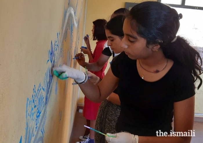 Students, and volunteer artists paint the walls of the refectory of the Magnificat Centre.