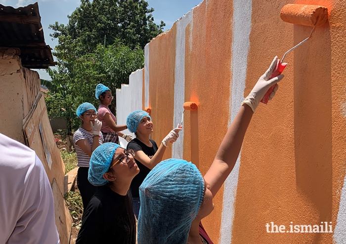 Young volunteers from Kampala work together to repaint the Kyanja Muslim Nursery School.