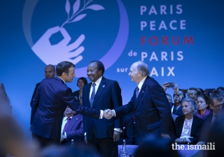 President Emmanuel Macron welcomes Mawlana Hazar Imam to the opening session of the Paris Peace Forum while President Paul Biya of Cameroon looks on.