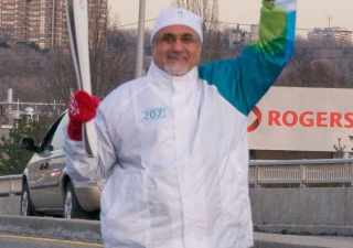 President Manji waves at the residents of Don Mills as he carries the Olympic Torch along York Mills Road in Toronto.