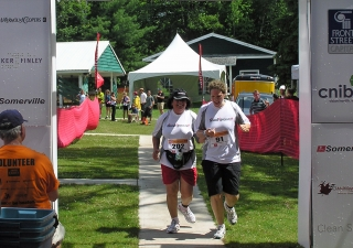Rozina Issani and her guide Kate cross the finish line at the third annual Joe's Team Triathlon in Muskoka, Ontario.