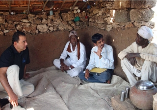 Munir Samji speaks with to two Siddhi farmers. With advice and assistance from AKRSP, many of the farmers have improved in their income from the land — in some cases doubling it.