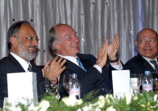 Mawlana Hazar Imam applauds during the institutional dinner, together with Ismaili Council President Aitmadi Zul Abdul and AKDN Resident Representative Aitmadi Aziz Bhaloo.