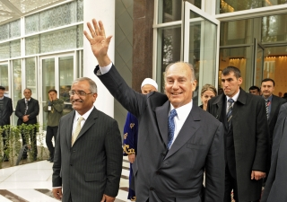 As he departs the Dushanbe Serena Hotel, Mawlana Hazar Imam waves at members of the Jamat gathered across the street.