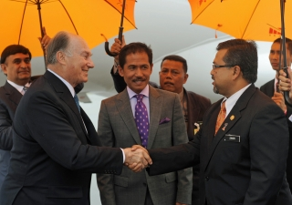 Mawlana Hazar Imam is received by Mr Zakri Jaafar, Malaysia's Undersecretary for the Organisation of Islamic Cooperation, as Dato' Naimun Ashakli Mohammad, Chief of Protocol and Consular from the Malaysian Ministry of Foreign Affairs looks on.