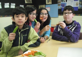 Children at Bait-ul Ilm snack on a healthy plate of vegetables.