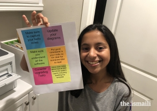 Nabeela Talib displays an example of the product of her computer code, which sends messages from her phone to her printer to print sticky notes.