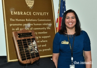 Sharmin Barolia stands in front of a plaque with the names of past honorees of the Embrace Civility Award.